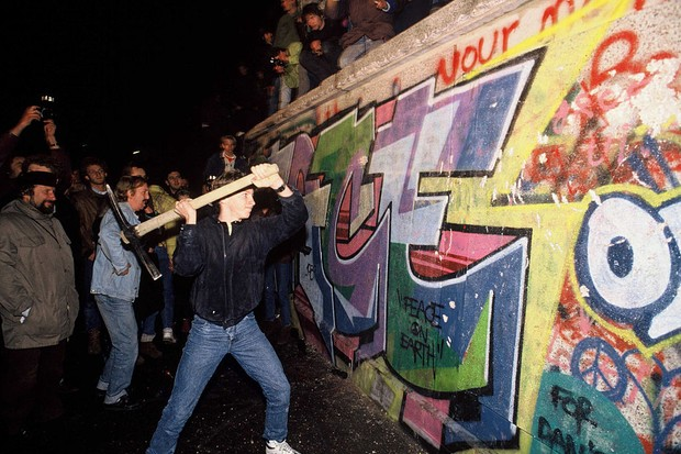 A man attacks the Berlin Wall with a pickaxe on the night of November 9th, 1989 as news spread rapidly that the East German Government would now start granting exit visas to anyone who wanted to go to the West. The announcement was misinterpreted as meaning the border was now open and East German border guards were unable to stop the rush of people to the Wall. Within hours people were smashing sections of the Wall with their own hand tools and these first cracks in the Wall led to the complete opening of the border within days. (Photo by robert wallis/Corbis via Getty Images)