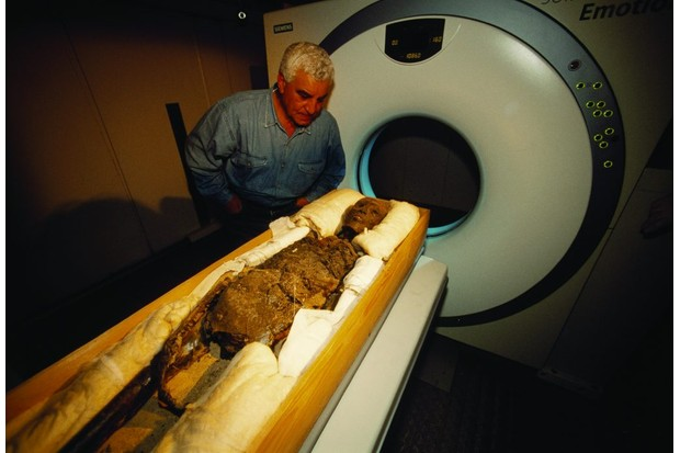 Tutankhamun's mummy enters a CT scanner.