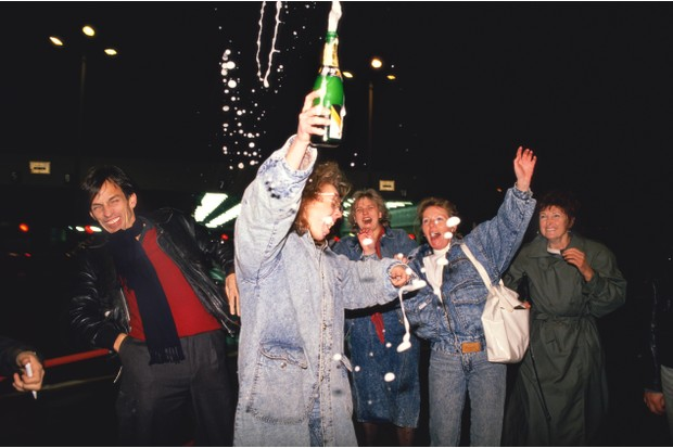 A group of five Germans celebrates with champagne as a section of the Berlin Wall is breached