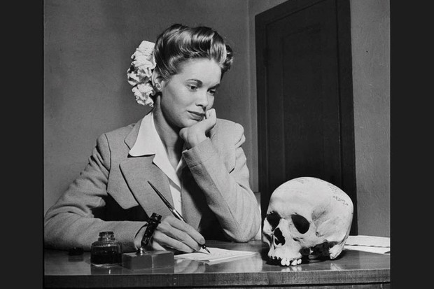A young American woman gazes at a human skull, sent to her by a boyfriend during WW2