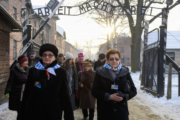 Auschwitz survivors and other visitors walk beneath the infamous sign above the camp gates