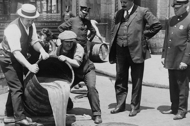 New York City police watching agents pour liquor into a sewer