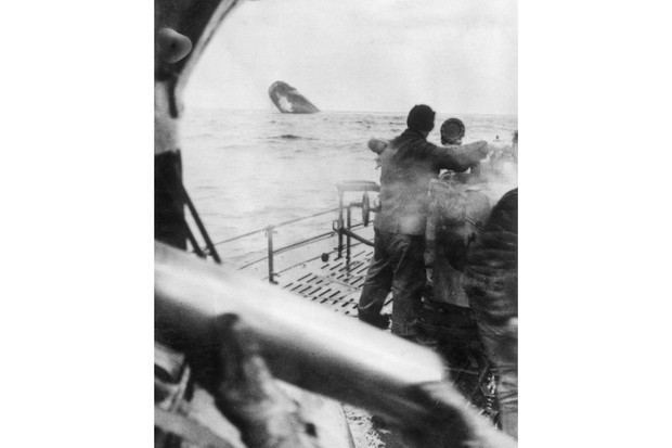 A U-boat crew watches as an Allied vessel sinks after hitting it with a deck gun, having already torpedoed the shi