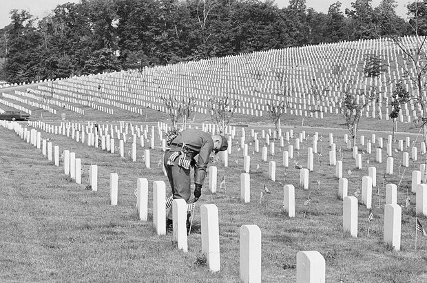 Tradition has it that small American flags are placed on war graves by a soldier in preparation for Memorial Day.
