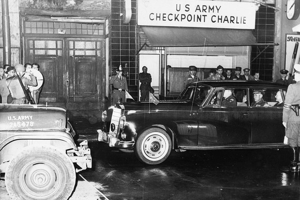 c1962: Military personnel in a car pass through the US Army's Checkpoint Charlie on the Berlin Wall. (Photo by Keystone/Getty Images)