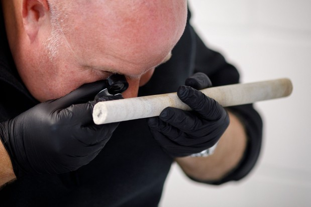 Professor Dave Nash analysingthe sarsen core extracted from Stone 58 at Stonehenge. (Photo by Sam Frost English Heritage)