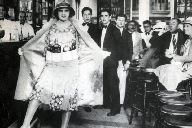 A flapper shows off her hidden bottles of alcohol
