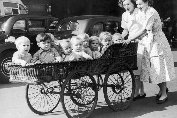 Babies from a nursery are walked in a pram, c1953