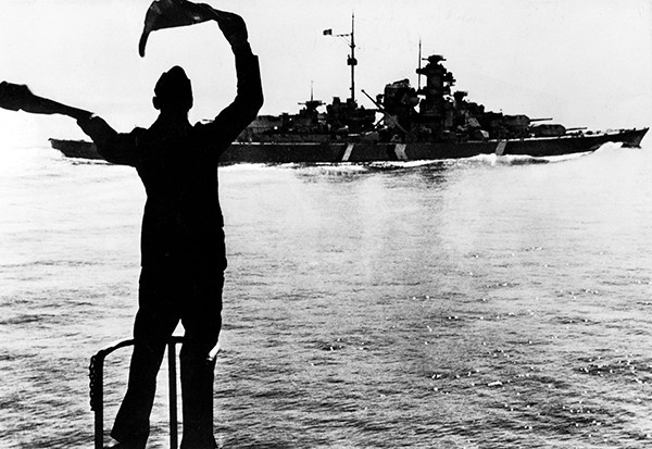 A German sailor signals Bismarck during manoeuvres in the western Atlantic, some time before the British gave chase. The maimed battleship sank below the waves on 27 May 1941