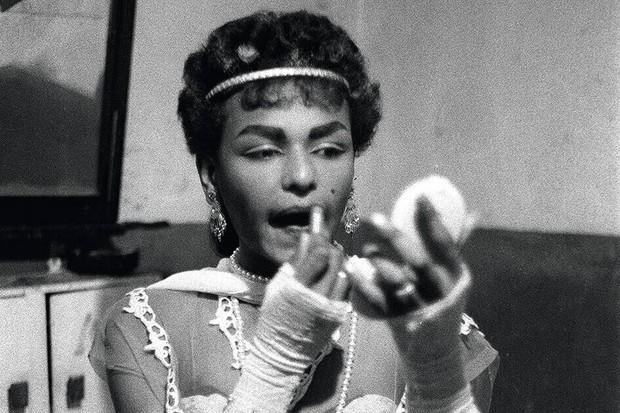 A drag queen applies lipstick in this 1959 photograph