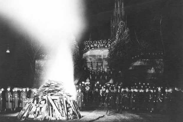 Black and white image showing soldiers of the Third Reich surround a huge bonfire