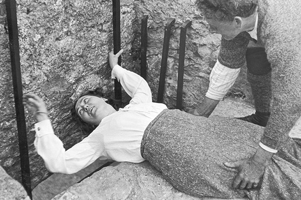 Kissing the Blarney Stone: a women hangs over the precipice with the aid of a friend as she attempts the feat at Blarney Castle in 1935
