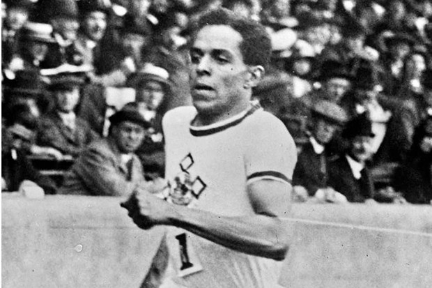 A man runs on an athletics track with a crowd behind him
