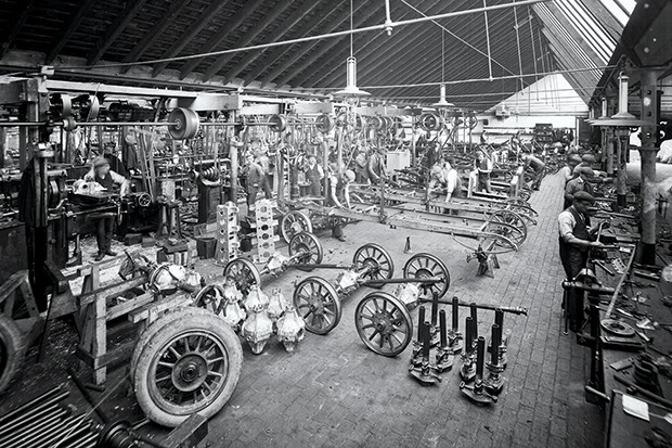 Axles and other car parts are laid out on a factory floor ready for assembly, with men working around them