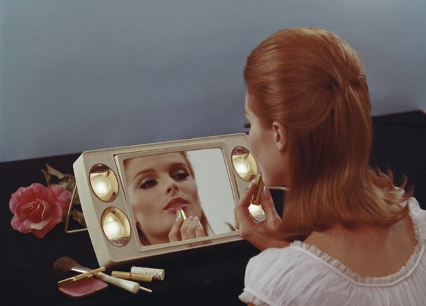 A young woman sat in front of a mirror applies lipstick, 1967