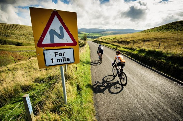 Cyclists ride pass a road sign warning of sharp bends