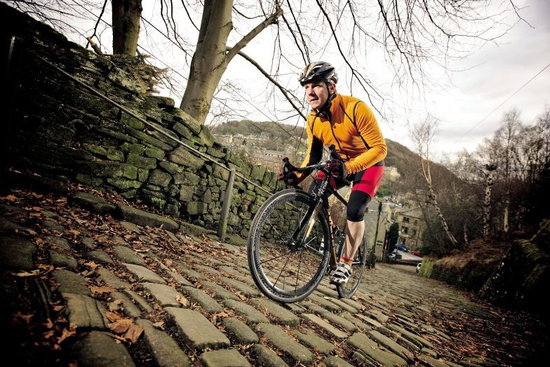 One cyclist climbing on cobbles in Yorkshire