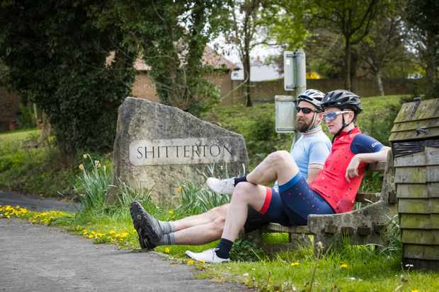 Two cyclists sit on a bench by the sign at the entrance to the village of Shitterton