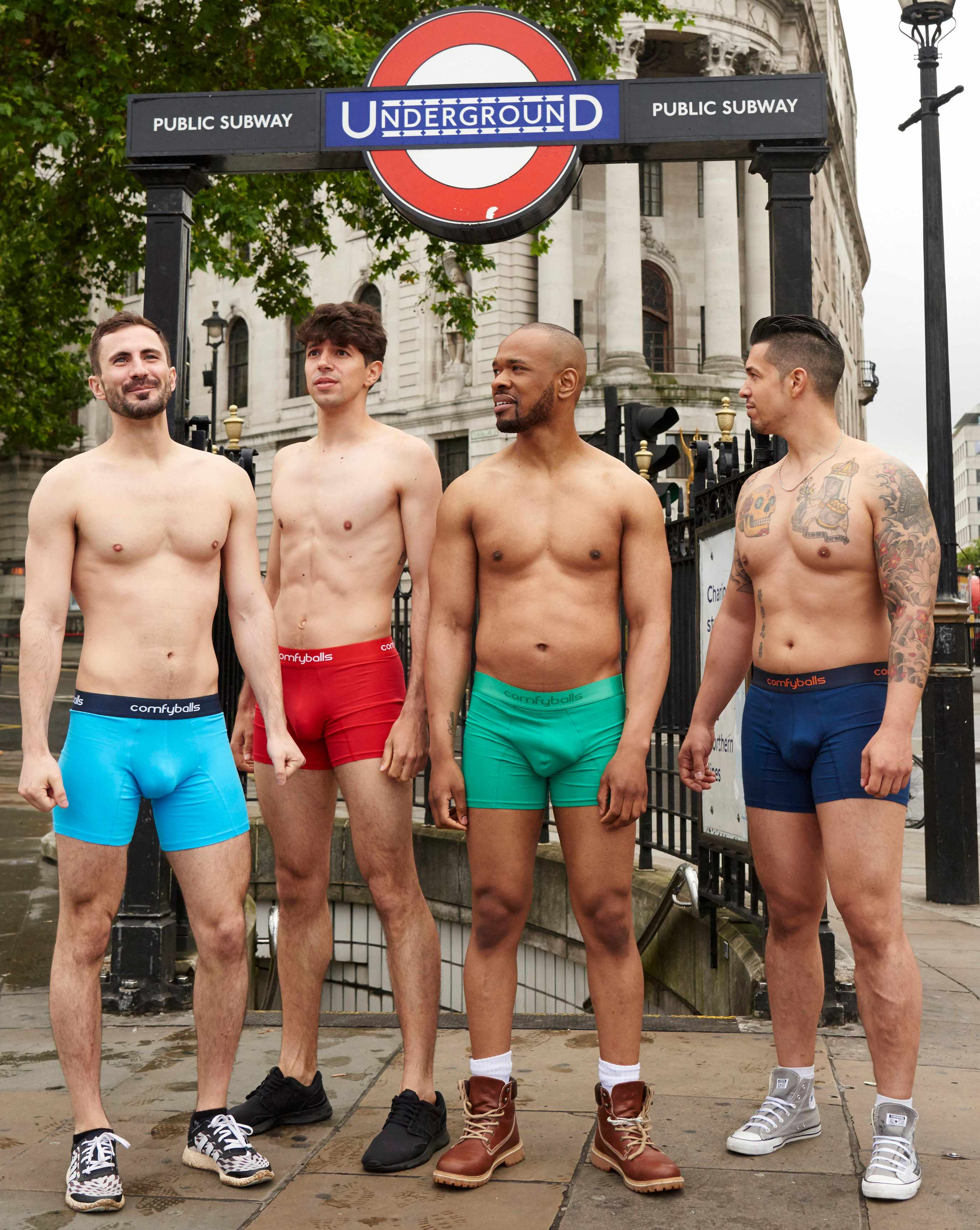 Four men in Comfyballs Underpanst stand in front of a London Underground station