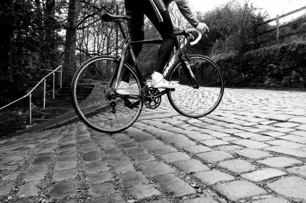 Black and white image of cyclist on teh cobbled Shibden Wall climb
