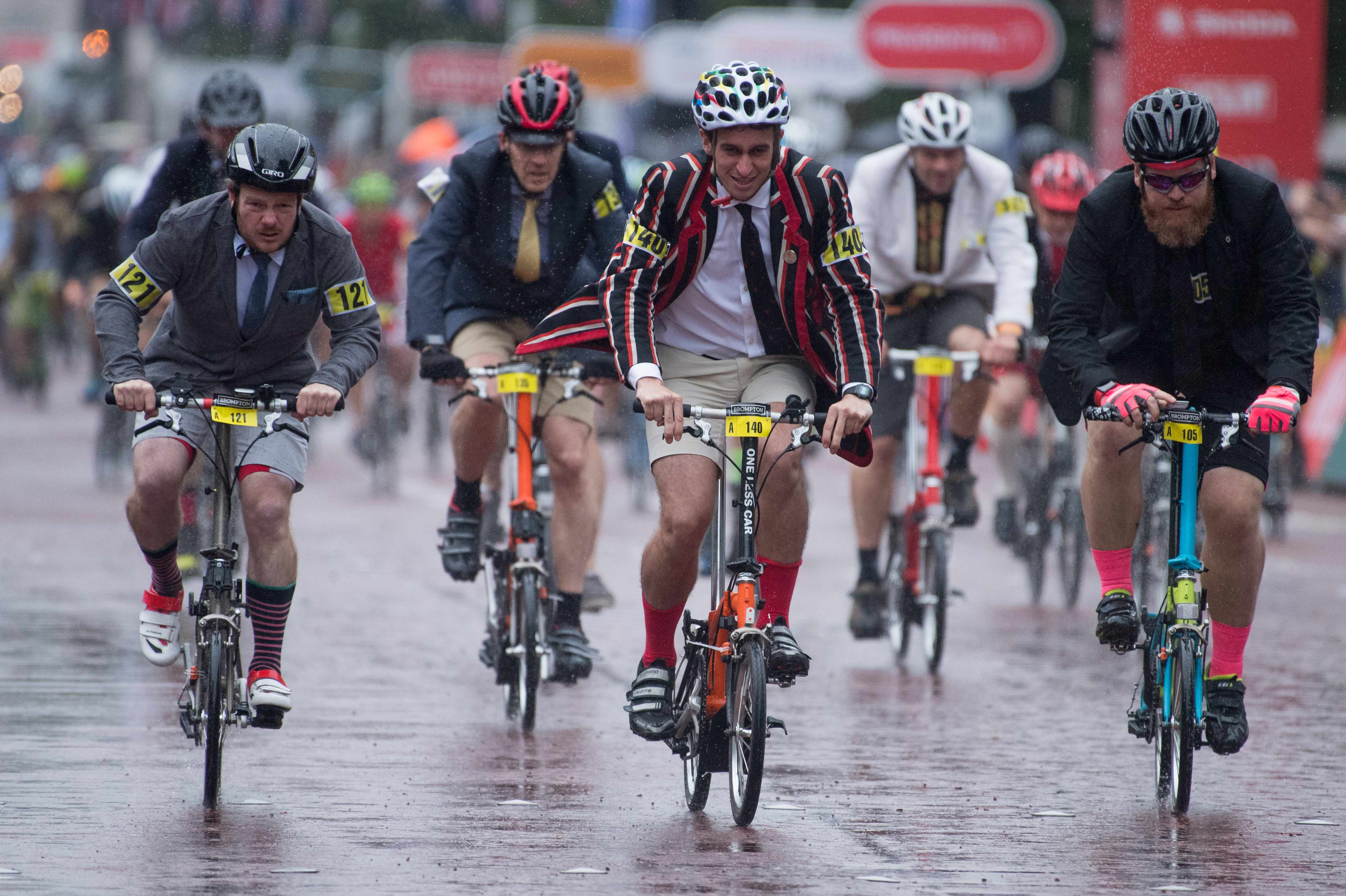 A man in a stripy blazer races his folding bike at the Brompton World Championships 2018