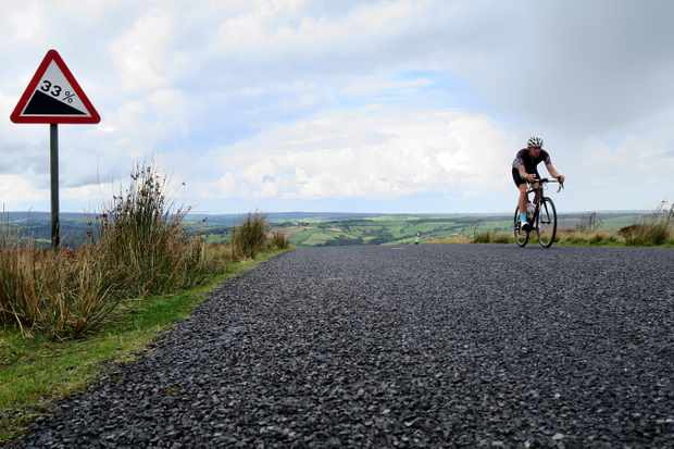 Simon Warren on a road bike climbing a hill