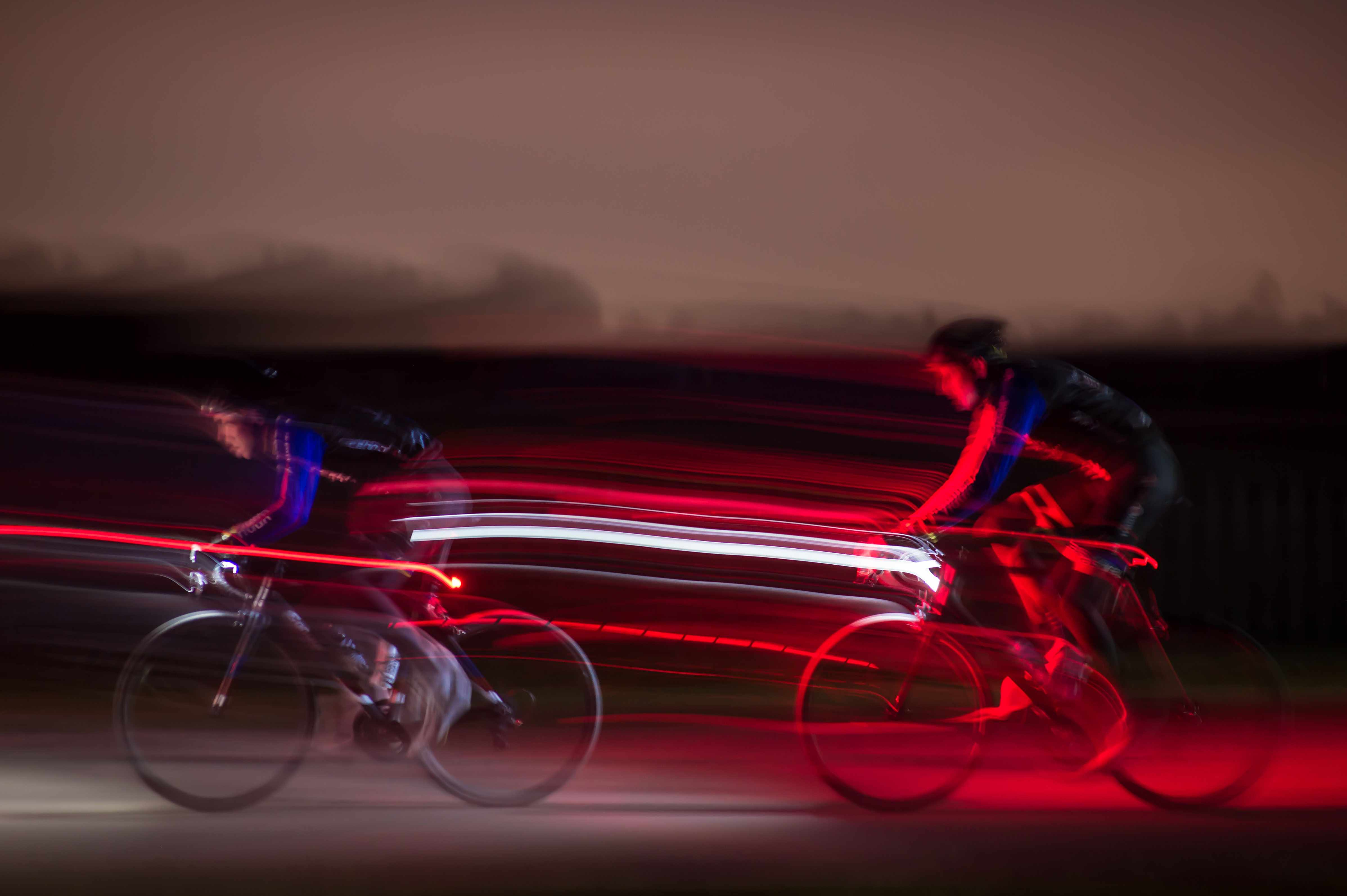 Two cyclists riding in the dark light trail