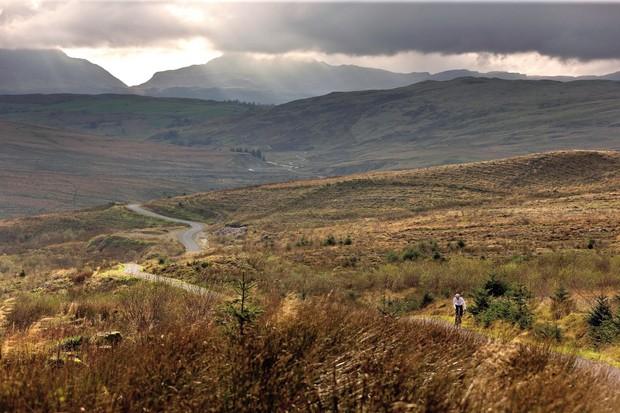 Cyclist riding across moors near Bala in North Wales