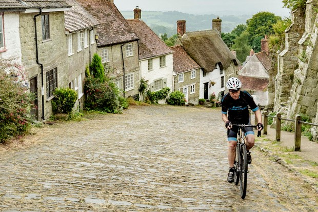 Cyclist climbs Gold Hill, Shaftesbury, Dorset on Kinesis bike