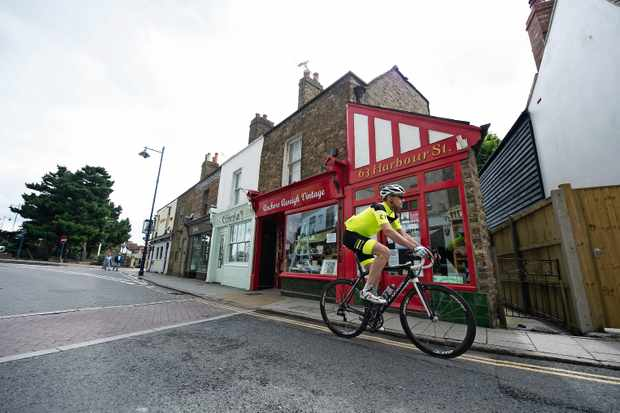 Cyclist riding past colourful shop front in Kent