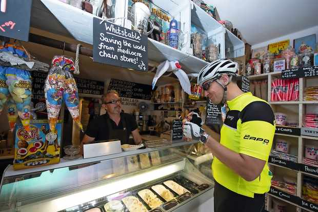 Cyclist buying an ice cream in Whitstable, Kent