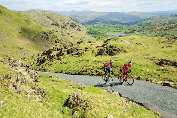 Two cyclists climbing Wrynose Pass in the Lake District