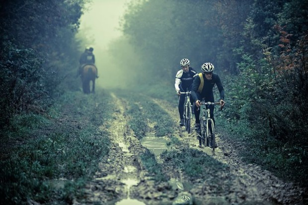 Two cyclists pass a horse on a very muddy stretch of the Ridgeway