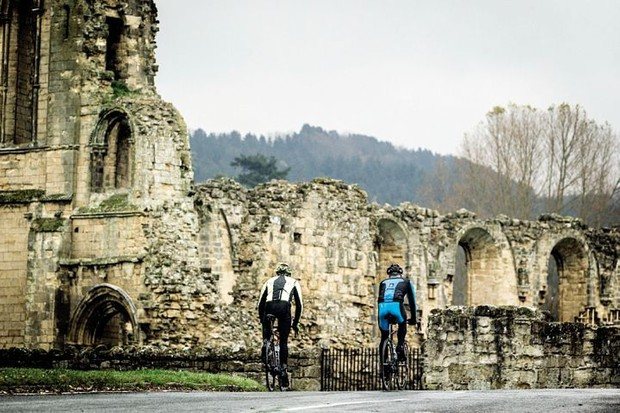 Two cyclists riding past the ruins of an abbey in the North Yorkshire Moors