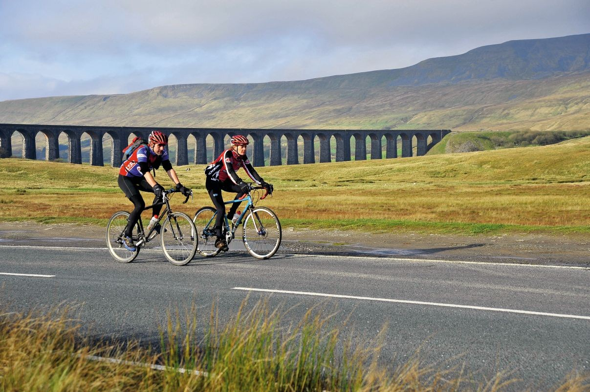Cyclists with the iconic Ribblehead viaduct on the Settle to Carlisle railway in the background