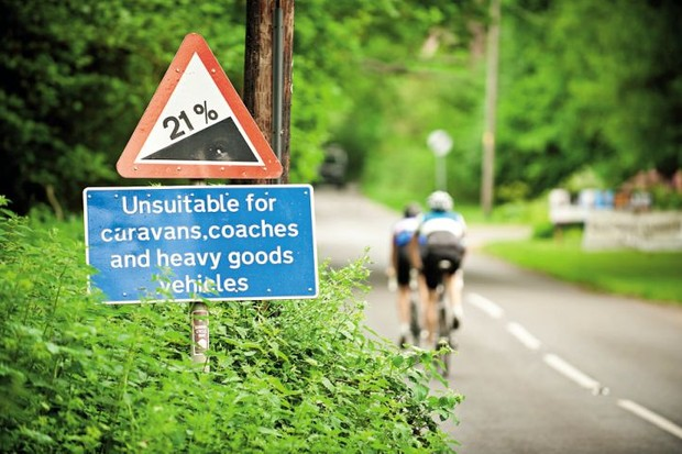 Two cyclists ride past a 21% gradient sign in the Surrey Hills