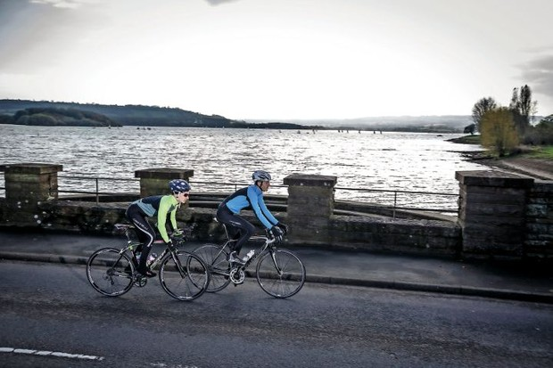 Two cyclists ride past water in Somerset