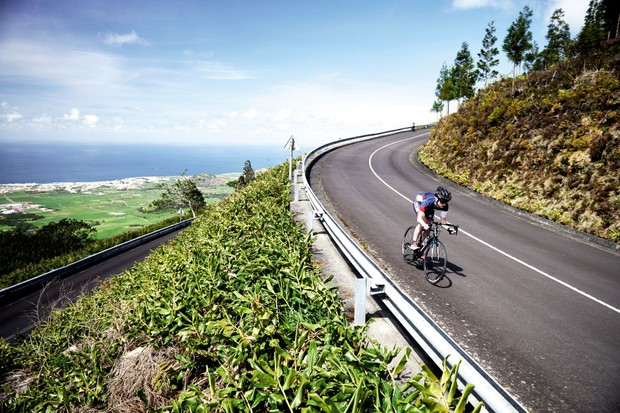 A cyclist swoops downhill on a smooth road in the Azores
