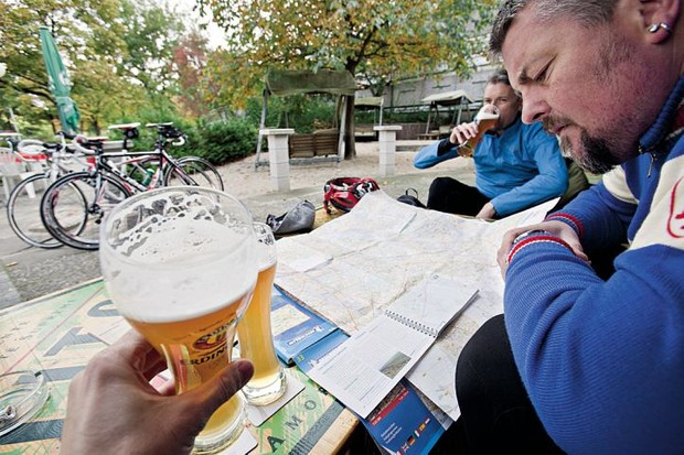 Cyclists drinking beer and looking at maps in Berlin Germany