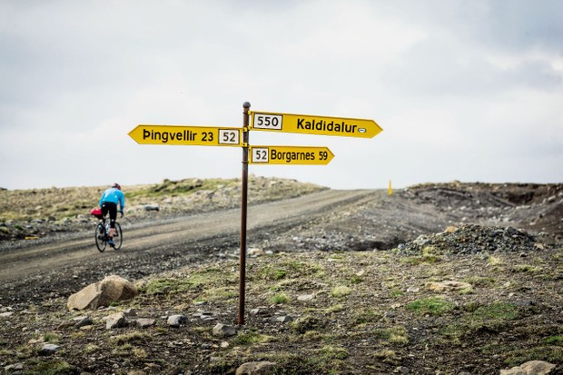 Cycling past roadsigns in Iceland