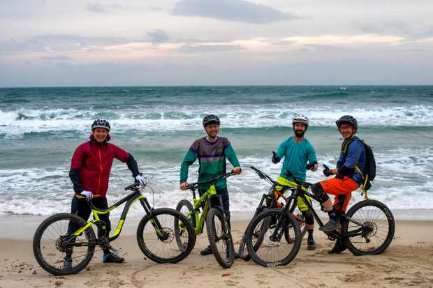MBUK team on the beach with bikes in Punta Ala