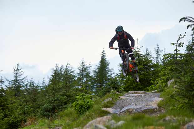 Al Evans jumping his Orange Segment Pro at Glentress