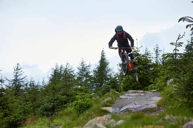 Al Evans jumping his Orange Segment Pro at Glentress