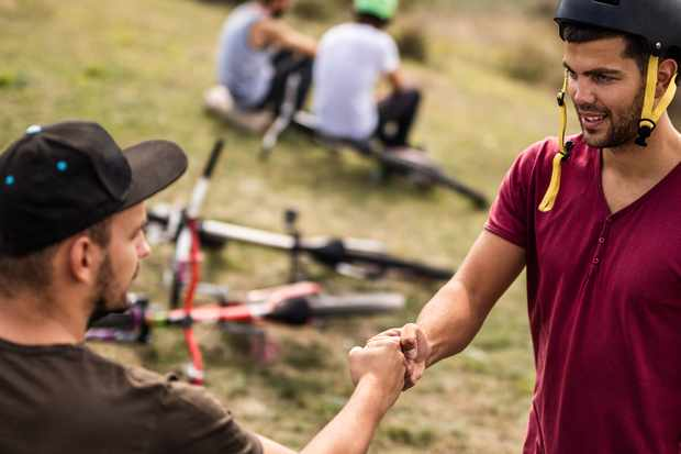 two mountain bikers doing a fist bump