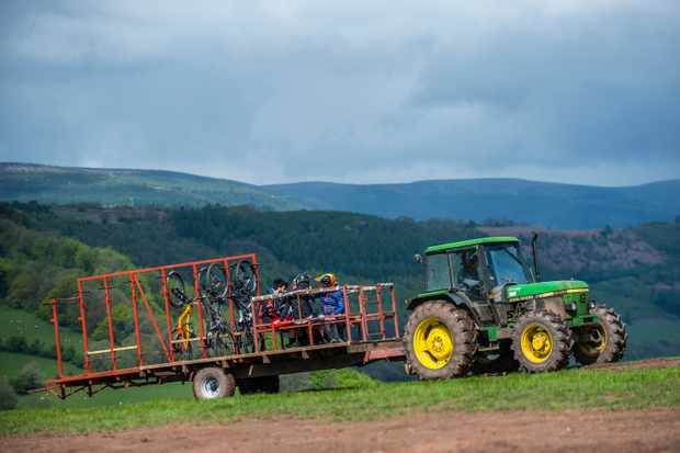 Riders sitting in the back of an uplift trailer being towed up by a tractor