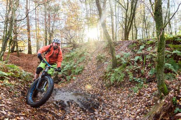 Man fatbiking round boggy section in the woods