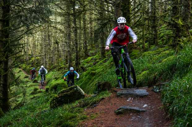 Leo Houseman leads out Ed Thomsett, Joe Breeden and Alex Evans on an MBUK Wrecking Crew photoshoot in Penmachno, North Wales. They're riding through a lush green forest.