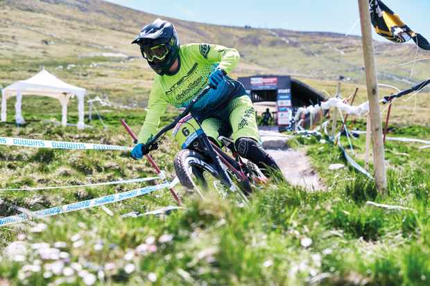 Joe Breeden who rides for Intense Cycles UK hits the first turn on the Fort William downhill track in the sunshine