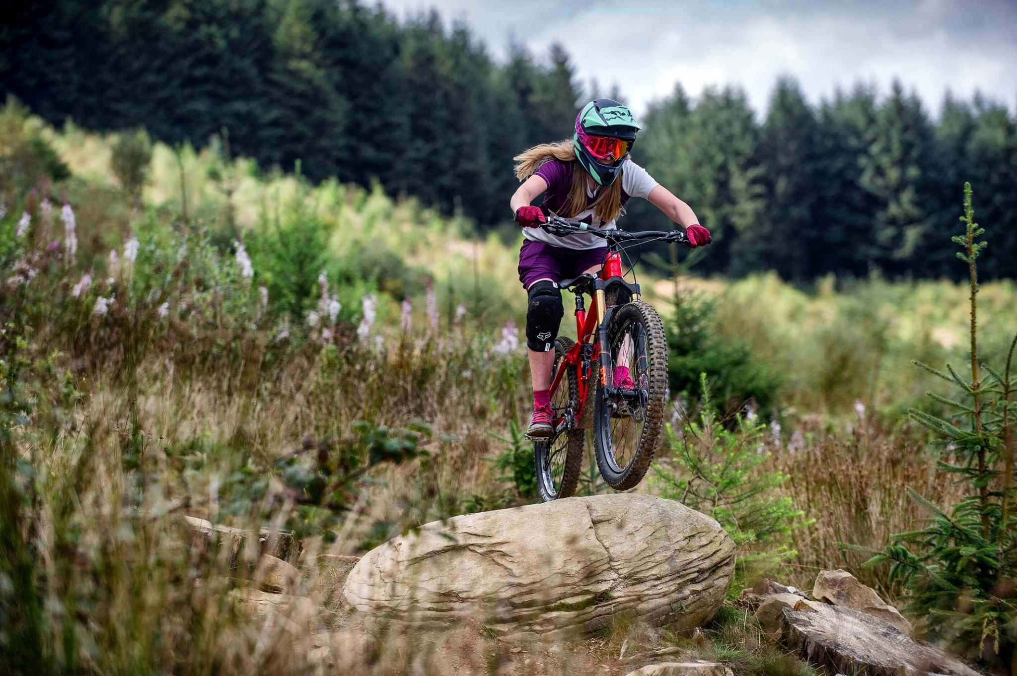 female rider jumps over rock at bikepark wales