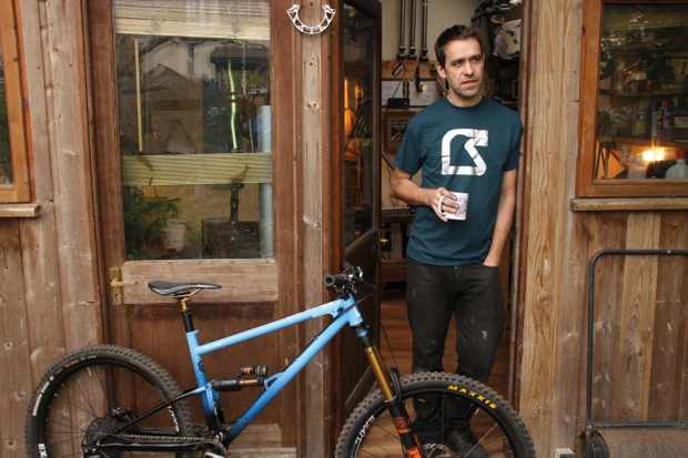 Joe McEwan of Starling Cycles poses with a cup of tea outside his Bristol Workshop